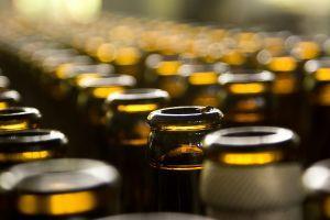 Pruunist klaasist avatud õlupudelite read