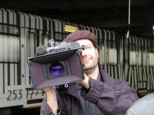 Mees  vaatajale suunatud telekaameraga õlal, filmimas