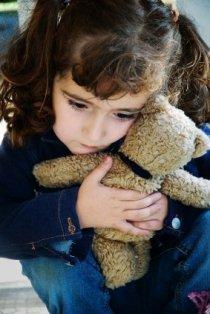 Tumeda juustega väike tüdruk kaisutab mängukaru