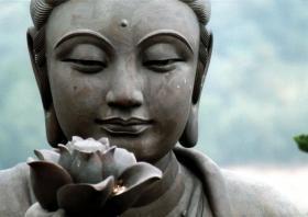 Buda suletud silmadega ja lillega peopesal