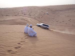 Kaks meest valgetes riietes istuvad liivamäe tipul kõrbes