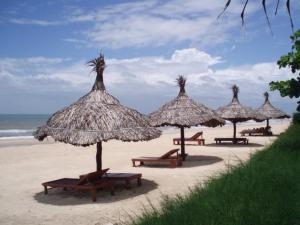 Troopiline supelrand ja õlast tehtud päikesevarjude rida