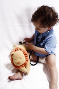 Väikelaps mängib arsti pehme mänguasjaga