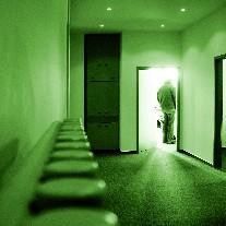tume koridor ja inimese siluett avatud ukse ees
