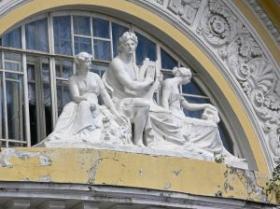 Klassikalises stiilis kolme skulptuuri grupp hoone fassaadil