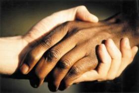 Tumedanahalise inimese käsi valge inimese käes