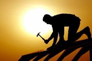 töömees haamriga töötab katusel